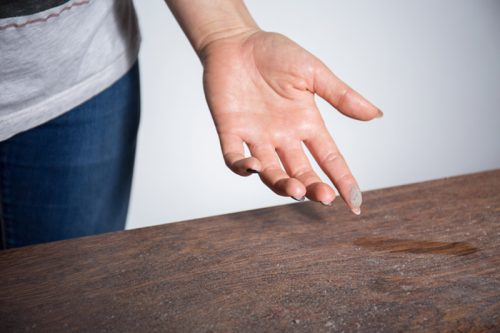 Close-up of dust on woman finger taken from wooden table in Bowling Green, Ohio